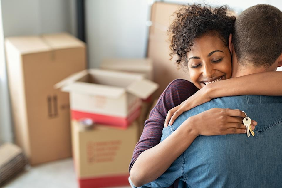 A couple hug after buying their own home