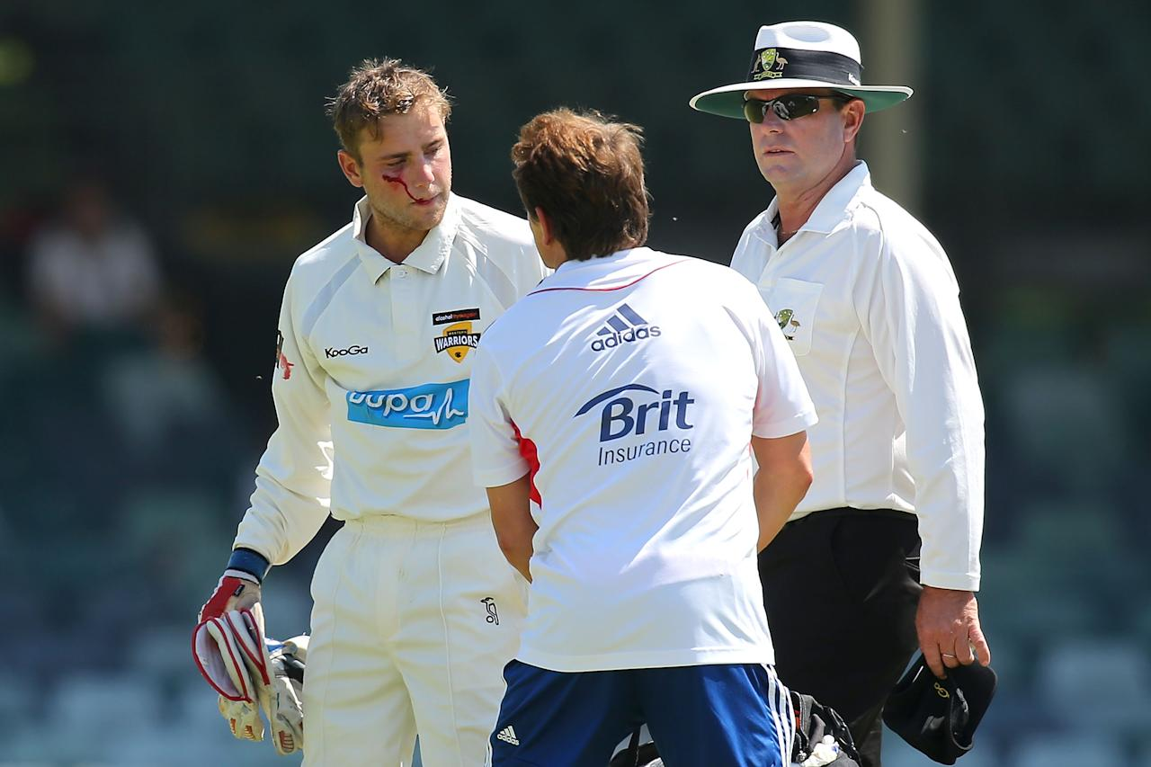 PERTH, AUSTRALIA - NOVEMBER 01:  Tom Triffitt of the WA Chaiman's XI receives assistance from an English trainer after being hit in the face by the ball during day two of the Tour match between the WA Chairman's XI and England at WACA on November 1, 2013 in Perth, Australia.  (Photo by Paul Kane/Getty Images)