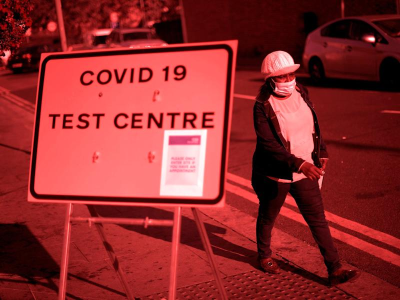 Pedestrian wearing facemask walks past a sign for a Covid-19 test centre in Leyton, east London on 19 September (AFP via Getty)