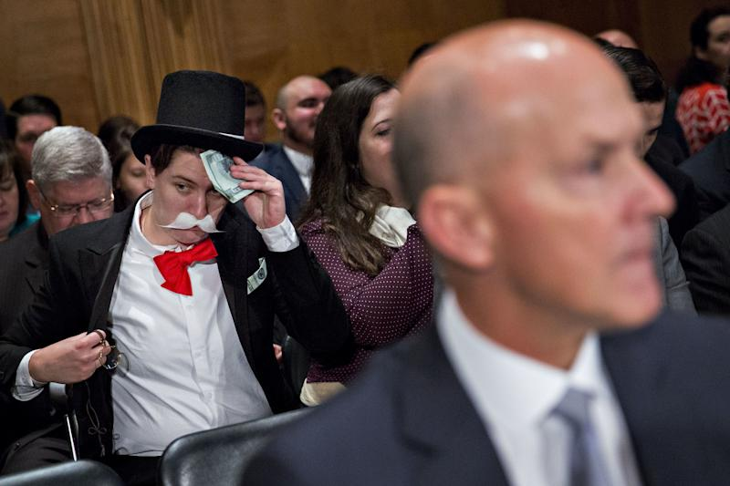 A demonstrator sits in costume behind Richard Smith, former chairman and chief executive officer of Equifax Inc., right, before a Senate Banking Committee hearing in Washington, D.C., on Wednesday, Oct. 4, 2017.