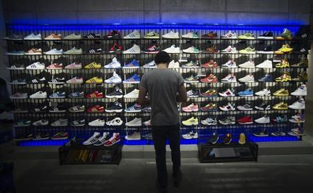 A man stands in front of a rack with Adidas Original shoes before the opening at the new Adidas Originals store in Berlin