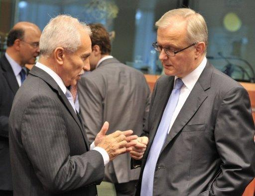 Cyprus' Finance Minister Vasos Shiarly (L) speaks with European Union Commissioner for Economic and Monetary Affairs Olli Rehn before a Eurozone meeting. European Union finance ministers bought Spain more time to revive its sickly economy on Tuesday, offering 30 billion euros to save the country's banks and protect Europe from more debt contagion