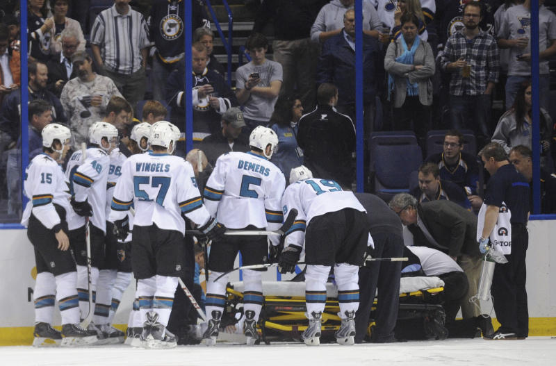 San Jose Sharks watch as teammate Dan Boyle is placed onto a stretcher during the first period of an NHL hockey game against the St. Louis Blues on Tuesday, Oct. 15, 2013, in St. Louis. Boyle suffered a head injury. The Sharks won 6-2. (AP Photo/Bill Boyce)