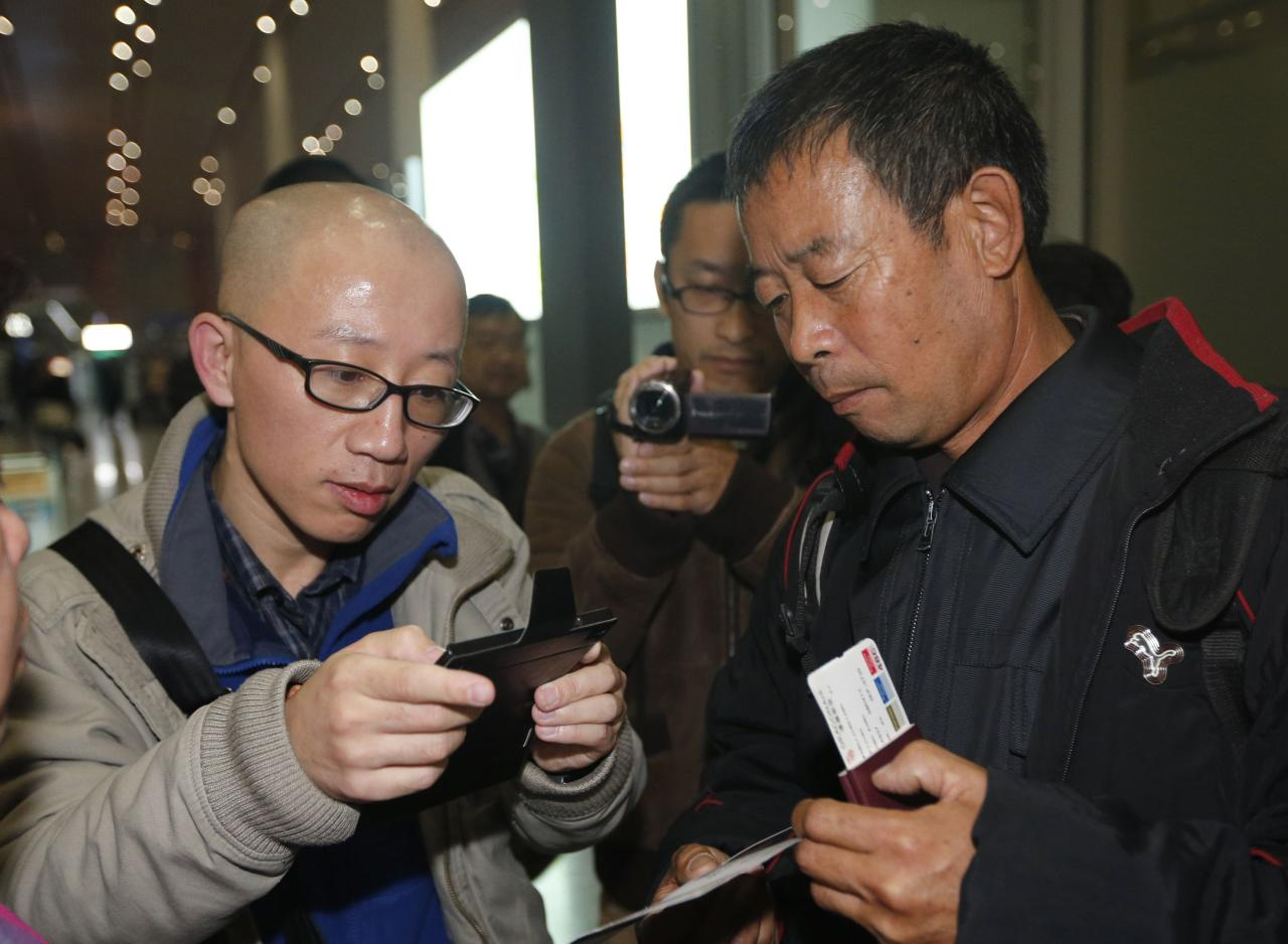 Chinese dissident Hu Jia (L) uses his mobile phone as he talks with Chen Guangfu, brother of Chinese political dissident Chen Guangcheng, who is leaving for the U.S. to meet Chen, at Beijing airport in this November 6, 2013 file photo. To match story CHINA-ACTIVIST/ REUTERS/Kim Kyung-Hoon/Files (CHINA - Tags: CRIME LAW POLITICS)