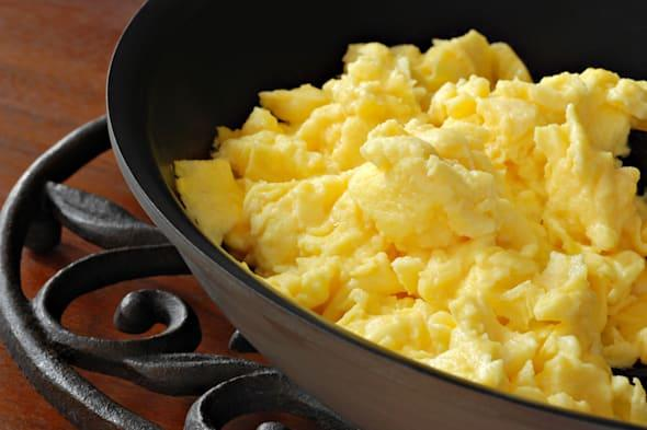 Freshly prepared scrambled eggs in healthy, eco friendly, ceramic nonstick skillet on trivet.  Macro with shallow dof.