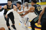 Denver Nuggets guard Markus Howard, center, loses control of the ball while driving between Memphis Grizzlies guards Tyus Jones, left, and Desmond Bane in the second half of an NBA basketball game Monday, April 26, 2021, in Denver. (AP Photo/David Zalubowski)