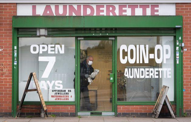 A man cleans the windows of a launderette in Leicester, England.