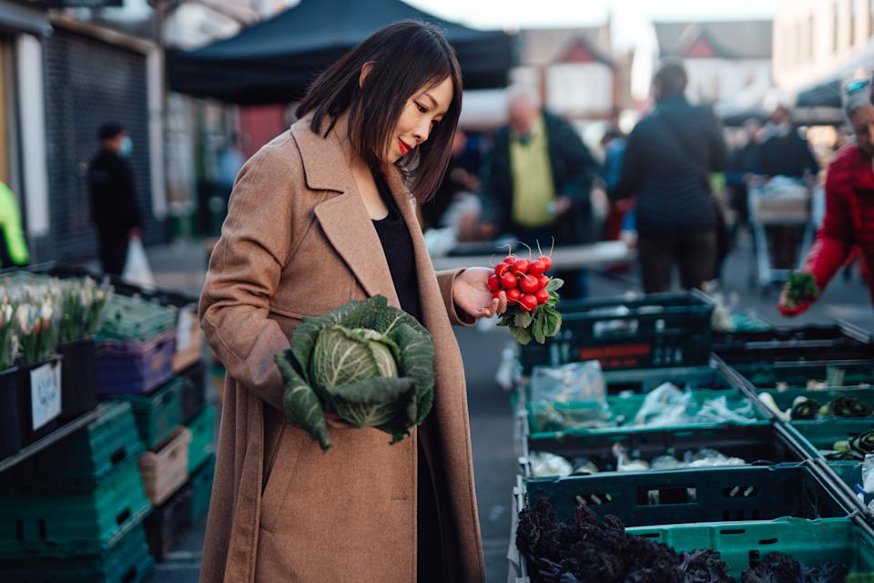 Young Asian woman shopping for fresh organic vegetables at local farmer market. Putting a cabbage and raddish into an eco-friendly cotton mesh shopping bag. Zero waste concept. Local businesses idea. Local food market.