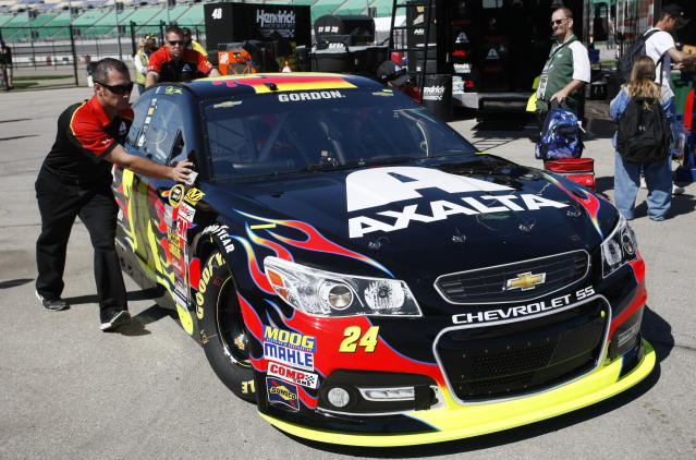 Crew members push the car of Jeff Gordon (24) to his garage Friday, May 9, 2014, at Kansas Speedway in Kansas City, Kan., for Saturday night's NASCAR Sprint Cup series auto race. (AP Photo/Colin E. Braley)