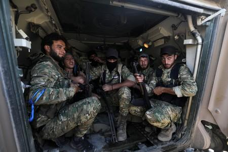 Turkey-backed Syrian rebel fighters sit inside a military vehicle near the border town of Tel Abyad