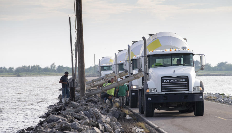 Terrebonne Parish employees work against time shoring up Levee Road in Isle de Jean Charles, La., with cement and rocks ahead of Hurricane Delta Wednesday, Oct. 7, 2020. Delta could make landfall, possibly as a Category 3 storm, sometime Friday south of Morgan City, La. (David Grunfeld/The Advocate via AP)