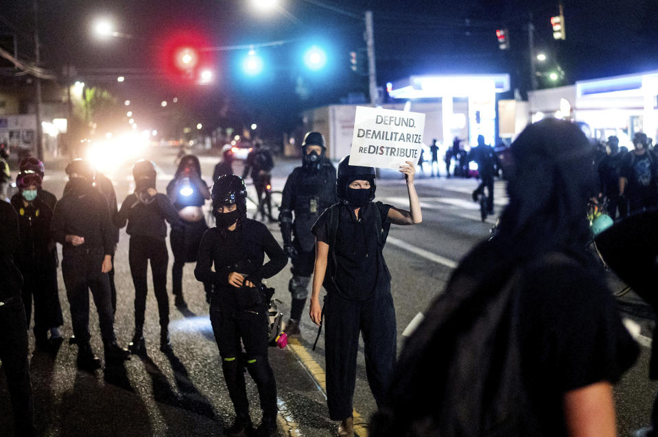 Anti-police protesters rally outside the Portland Police Association building on Friday, Sept. 4, 2020, in Portland, Ore. This weekend Portland will mark 100 consecutive days of protests over the May 25 police killing of George Floyd.  (AP Photo/Noah Berger)