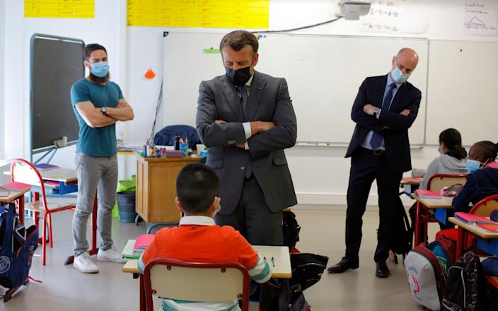 French President Emmanuel Macron talks with a pupil while visiting a school in Melun, south of Paris - Thibault Camus/AP