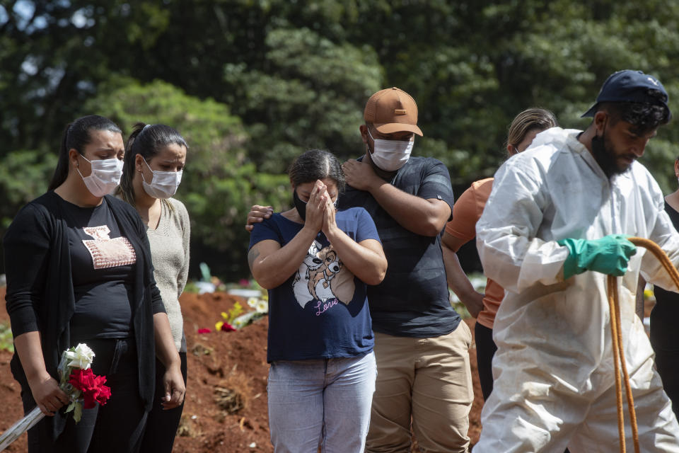 FILE - In this April 7, 2021, file photo, people attend the burial of a relative who died from complications related to COVID-19 at the Vila Formosa cemetery in Sao Paulo, Brazil. Nations around the world set new records Thursday, April 8, for COVID-19 deaths and new coronavirus infections, and the disease surged even in some countries that have kept the virus in check. Brazil became just the third country, after the U.S. and Peru, to report a 24-hour tally of COVID-19 deaths exceeding 4,000. (AP Photo/Andre Penner, File)