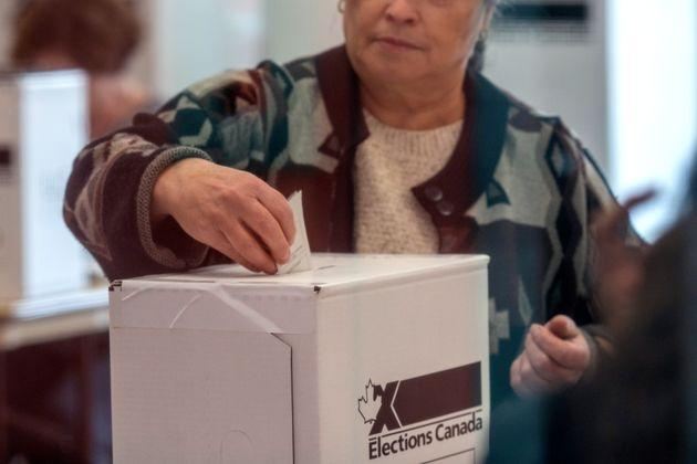 A woman votes at a polling station in Toronto for the federal election, Oct. 21, 2019.