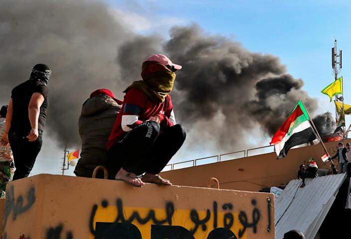Pro-Iranian militiamen and their supporters set a fire during a sit-in in front of the U.S. embassy in Baghdad, Iraq, Wednesday, Jan. 1, 2020. U.S. troops have fired tear gas to disperse hundreds of pro-Iran militiamen and other protesters who were gathered for a second day outside the American Embassy compound in Baghdad.