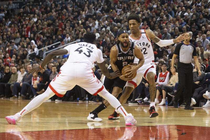 San Antonio Spurs' Patty Mills, center, drives between Toronto Raptors' Pascal Siakam and Patrick McCaw during first-half NBA basketball game action in Toronto, Sunday, Jan. 12, 2020. (Chris Young/The Canadian Press via AP)
