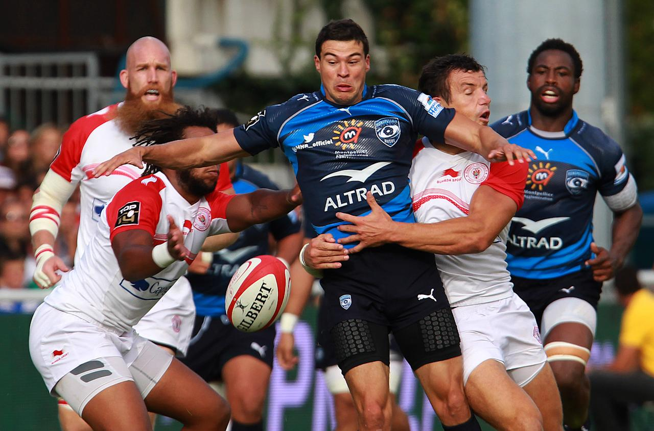 Montpellier's Anthony Floch, center, is tackled by Biarritz's Damien Traille, right, during their French Top 14 rugby union match at the Stade Aguilera, in Biarritz, southwestern France, Saturday Aug. 24, 2013. (AP Photo/Bob Edme)