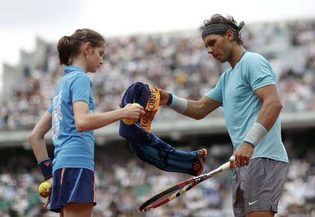 Rafael Nadal of Spain returns a towel to a ball girl during his men's singles match against Dusan Lajovic of Serbia at the French Open tennis tournament at the Roland Garros stadium in Paris June 2, 2014. REUTERS/Vincent Kessler