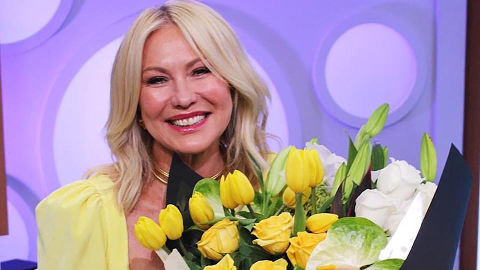 Kerri-Anne Kennerley wearing a yellow top and holding a bunch of yellow tulips