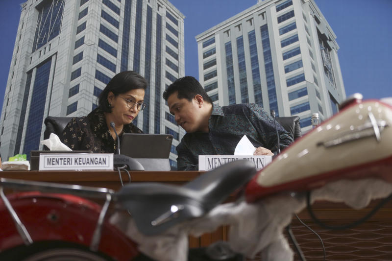 Indonesian Finance Minister Sri Mulyani Indrawati, left, confers with Minister of State-Owned Enterprises Eric Thohir as a Harley Davidson motorcycle, foreground, found by Customs officials on a Garuda Indonesia's new Airbus A330-900 being delivered from France is displayed during a press conference in Jakarta, Indonesia, Thursday, Dec. 5, 2019. Thohir said he will fire and seek the prosecution of the head of the national airline after he was implicated in the smuggling the motorcycle into the country on the new jet. (AP Photo/Achmad Ibrahim)