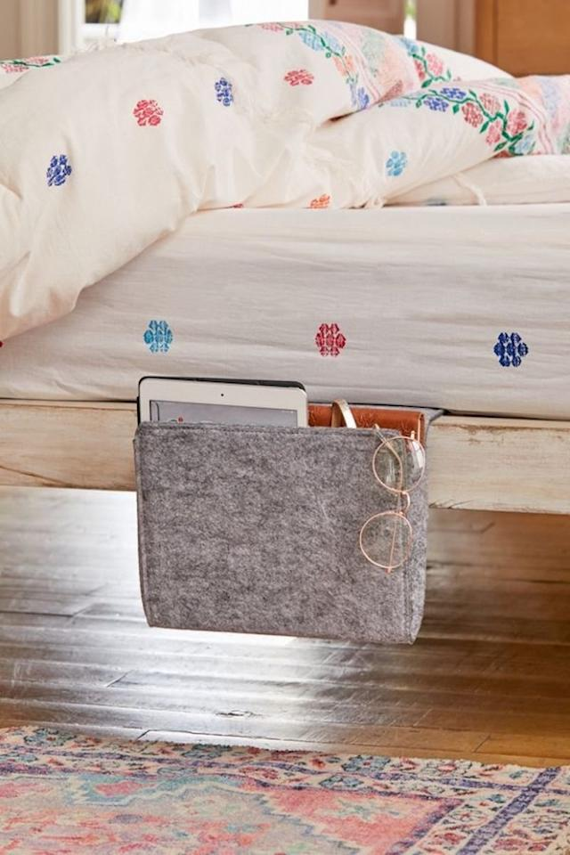 "<p>Crafted from gray felt, this sleek caddy is perfectly sized for keeping a book, a tablet, or a few magazines close to your bed. This clever organizer is a must-have for dorm rooms and small apartments. </p> <p><strong>To buy: </strong>$20, <a href=""https://click.linksynergy.com/deeplink?id=93xLBvPhAeE&mid=43176&murl=https%3A%2F%2Fwww.urbanoutfitters.com%2Fshop%2Fkikkerland-design-bedside-caddy&u1=RS%2C5CleverWaystoSneakMoreStorageUnderandAroundYourBed%2Ckholdefehr1271%2CORG%2CIMA%2C668762%2C201907%2CI"" target=""_blank"">urbanoutfitters.com</a>. </p>"