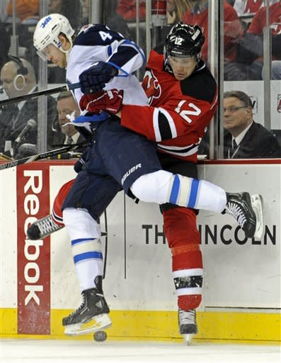 Winnipeg Jets' Paul Postma checks New Jersey Devils' Alexei Ponikarovsky (12), of Ukraine, during the second period of an NHL hockey game Sunday, Feb. 24, 2013, in Newark, N.J. (AP Photo/Bill Kostroun)