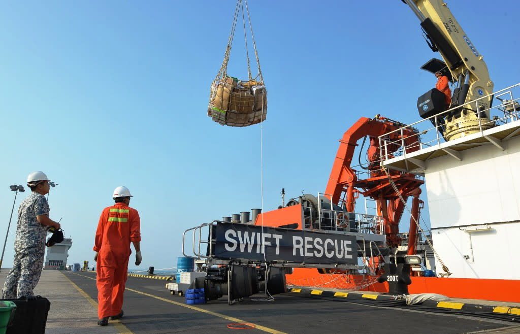 The Singaporean submarine support and rescue vessel, MV Swift Rescue, is prepared before it departs to assist in the search for missing Malaysian Airlines flight MH370 in Singapore, in this March 9, 2014 handout picture. Officials investigating the disappearance of a Malaysia Airlines jetliner with 239 people on board suspect it may have disintegrated in mid-flight, a senior source said on Sunday, as Vietnam reported a possible sighting of wreckage from the plane. REUTERS/Singapore MINDEF/Handout via Reuters (SINGAPORE - Tags: DISASTER POLITICS MILITARY) ATTENTION EDITORS - FOR EDITORIAL USE ONLY. NOT FOR SALE FOR MARKETING OR ADVERTISING CAMPAIGNS. THIS IMAGE HAS BEEN SUPPLIED BY A THIRD PARTY. IT IS DISTRIBUTED, EXACTLY AS RECEIVED BY REUTERS, AS A SERVICE TO CLIENTS