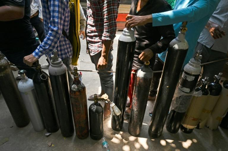 People wait in a line to refill oxygen cylinders for Covid-19 coronavirus patients in New Delhi