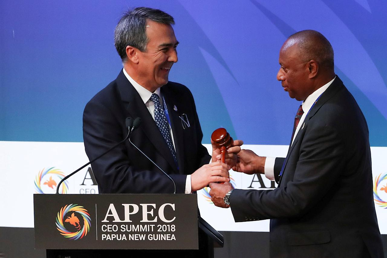 APEC CEO Summit 2018 chairman Isikeli Taureka (R) hands over the symbolic gavel to APEC CEO Summit 2019 chairman Jean-Paul Luksic of Chile during the APEC CEO Summit 2018 at Port Moresby, Papua New Guinea, 17 November 2018.  Fazry Ismail/Pool via REUTERS     TPX IMAGES OF THE DAY
