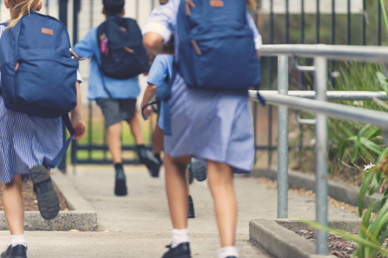 School children running away. They are wearing uniforms and carrying backpacks. They are having a race. Multi ethnic group with Asian, Caucasian and Aboriginal children. Rear view