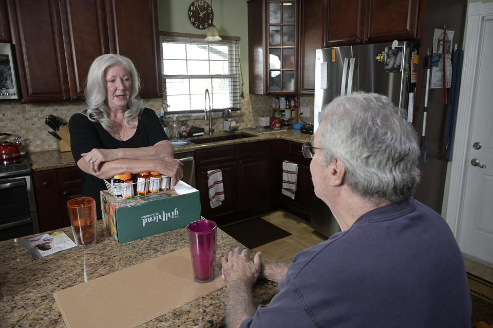 Retiree Donna Weiner, left, talks with her husband Norman Weiner at the kitchen table with the daily prescription medications that she needs and pays over $6,000 a year through a Medicare prescription drug plan at her home, Tuesday, Oct. 5, 2021, in Longwood, Fla. Weiner supports giving Medicare authority to negotiate drug prices. Negotiating Medicare drug prices is the linchpin of President Joe Biden's ambitious health care agenda. Not only would consumers see lower costs, but savings would be plowed into other priorities such as dental coverage for retirees and lower premiums for people with plans under the Obama-era health law. (AP Photo/Phelan M. Ebenhack)