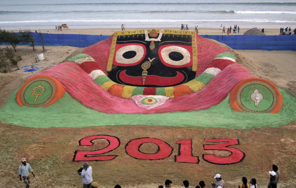 Visitors look at a sand sculpture designed to celebrate the 2013 new year by sand artist Sudarshan Pattnaik on the beach in Puri, about 65km (40 miles) from the eastern city Bhubaneswar in the Indian state of Odisha December 31, 2012.