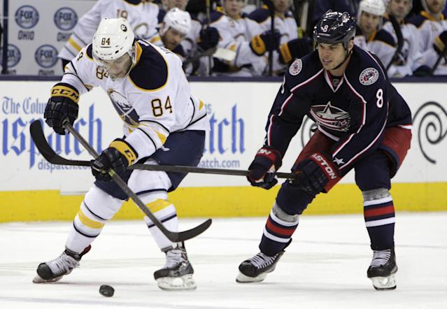 Buffalo Sabres' Philip Varone, left, carries the puck across the blue line as Columbus Blue Jackets' Nathan Horton defends during the third period of an NHL hockey game, Saturday, Jan. 25, 2014, in Columbus, Ohio. The Sabres won 5-2. (AP Photo/Jay LaPrete)