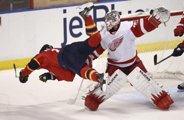 After hitting Detroit Red Wings goalie Jimmy Howard's (35) stick, Florida Panthers' Jesse Winchester falls to the ice during the third period of a NHL hockey game in Sunrise, Fla., Tuesday, Dec. 10, 2013. The Panthers won 3-2 in a shootout during overtime. (AP Photo/J Pat Carter)