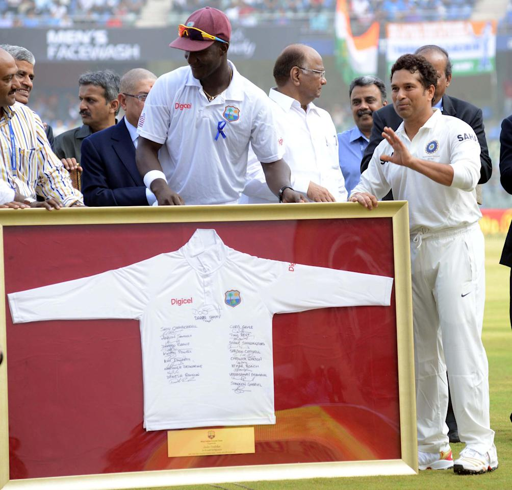 West Indian Captain Darren Sammy presents a memorabilia - a T-Shirt signed by all the West Indian players during his 200th and the last Test Match at Wankhede stadium in Mumbai on Nov.14, 2013. (Photo: Sandeep Mahankal/IANS)