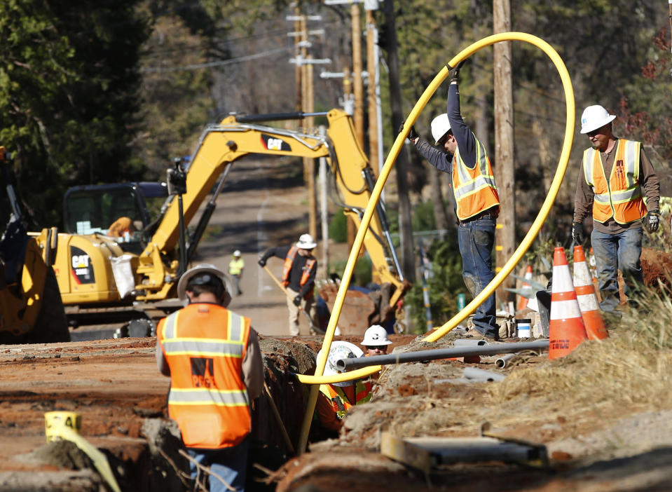 In this Thursday, Oct. 18, 2019, photo, Pacific Gas and Electric Company workmen bury utility lines in Paradise, Calif. Investigators say faulty electrical lines owned by PG&E ignited tinder-dry vegetation that resulted in the deadliest and most destructive wildfire in California history. The company is now burying their power lines underground. (AP Photo/Rich Pedroncelli)