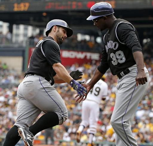Colorado Rockies' Michael McKenry, left, rounds third to greetings from Colorado Rockies third base coach Stu Cole (39) after hitting a solo home run off Pittsburgh Pirates starting pitcher Jeff Locke (49), center rear, during the second inning of a baseball game in Pittsburgh Sunday, July 20, 2014. (AP Photo/Gene J. Puskar)