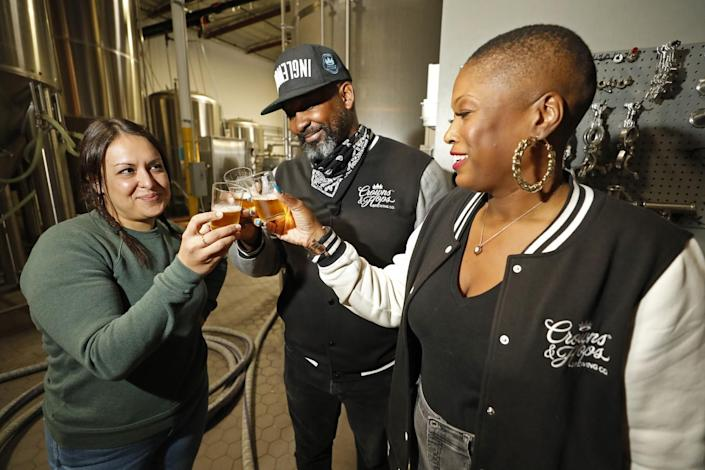 A man and two women toast with beer.