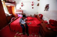 Iraqi teenager Hamid Saeed, who was mistreated by members of security forces, looks at his father's picture after being released from jail during an interview with Reuters at his home in Baghdad