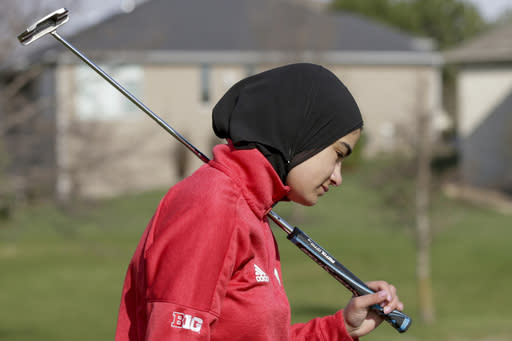 In this April 10, 2019 photo, Noor Ahmed, a member of the Nebraska NCAA college golf team, carries her putter during practice in Lincoln, Neb. Ahmed is the only golfer at the college level or higher known to wear a hijab while competing. She hopes Muslim girls are watching her and encouraged to chase their dreams in environments where they might encounter fear, uncertainty and hostility. (AP Photo/Nati Harnik)