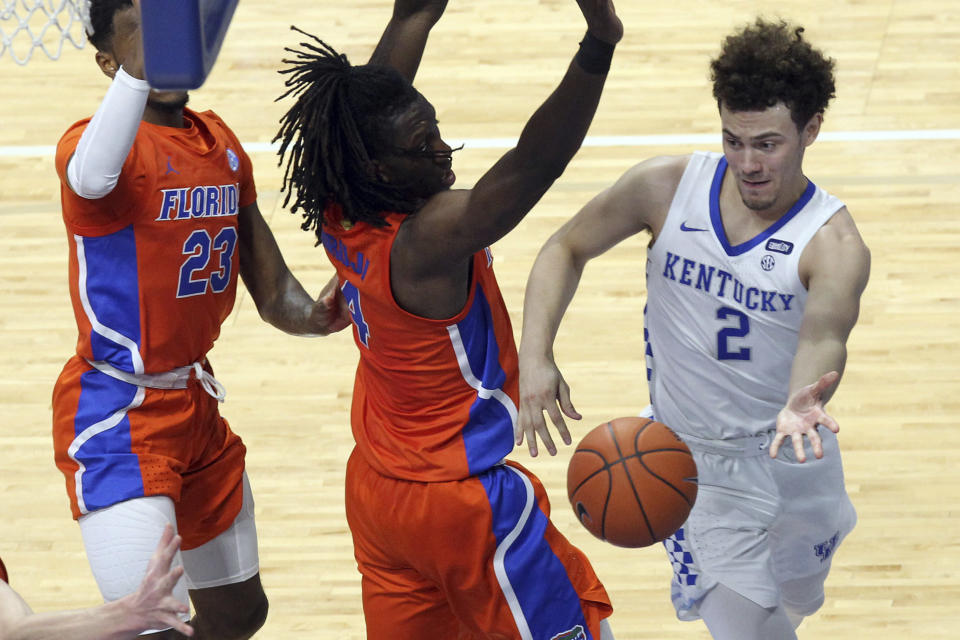 Kentucky's Devin Askew (2) passes around Florida's Anthony Duruji (4) and Scottie Lewis (23) during the second half of an NCAA college basketball game in Lexington, Ky., Saturday, Feb. 27, 2021. (AP Photo/James Crisp)