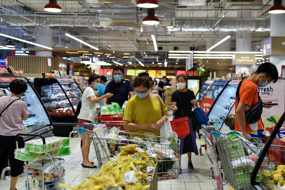 People shop for groceries at a supermarket after curbs on social gatherings and public activities were announced following a rise of coronavirus disease (COVID-19) cases in Singapore May 14, 2021. REUTERS/Caroline Chia