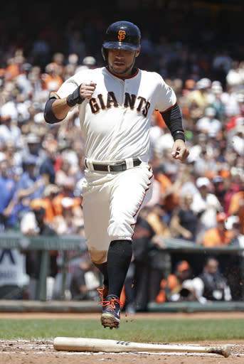San Francisco Giants' Gregor Blanco crosses home plate to score the Giants' first run in the third inning of their baseball game against the St. Louis Cardinals Thursday, July 3, 2014, in San Francisco. Blanco scored after Madison Bumgarner singled a line drive to left field. (AP Photo/Eric Risberg)