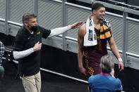 Loyola of Chicago head coach Porter Moser, left, walks off the court with Lucas Williamson after beating Illinois in a college basketball game in the second round of the NCAA tournament at Bankers Life Fieldhouse in Indianapolis Sunday, March 21, 2021. Loyola upset Illinois 71-58. (AP Photo/Mark Humphrey)