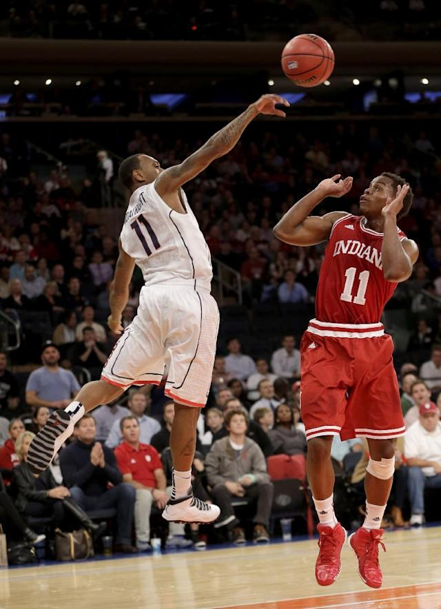 Connecticut's Ryan Boatright, left, keeps a ball in bounds over Indiana's Yogi Ferrell's head during the first half of an NCAA college basketball game on Friday, Nov. 22, 2013, in New York. (AP Photo/Seth Wenig)