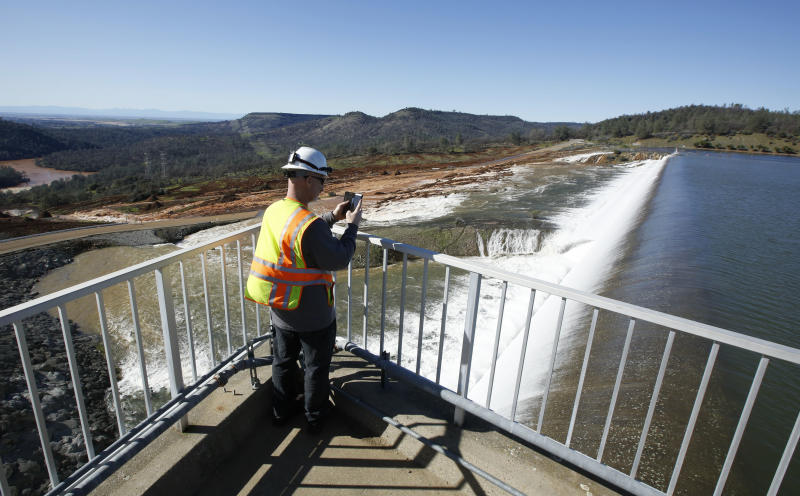 FILE - In this Saturday, Feb. 11, 2017, file photo, Jason Newton, of the Department of Water Resources, takes a picture of water going over the emergency spillway at Oroville Dam in Oroville, Calif. Over six days, operators of the tallest dam in the United States, struggled to figure out their next move after raging floodwaters from California's wettest winter in decades gouged a hole the size of a football field in the dam's main water-release spillway. (AP Photo/Rich Pedroncelli, File)