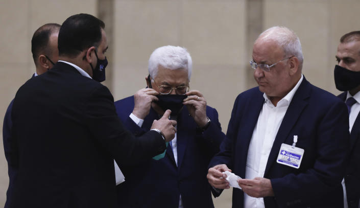 Palestinian President Mahmoud Abbas puts on a face mask as he heads a leadership meeting at his headquarters in the West Bank city of Ramallah on Tuesday, May 19, 2020. (Alaa Badarneh/Pool Photo via AP)