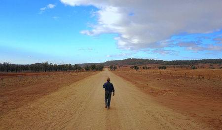 Farmer Ash Whitney walks down the middle of a road that divides his drought-effected property, located west of the town of Gunnedah, in north-western New South Wales in Australia, June 3, 2018. Picture taken June 3, 2018.    REUTERS/David Gray