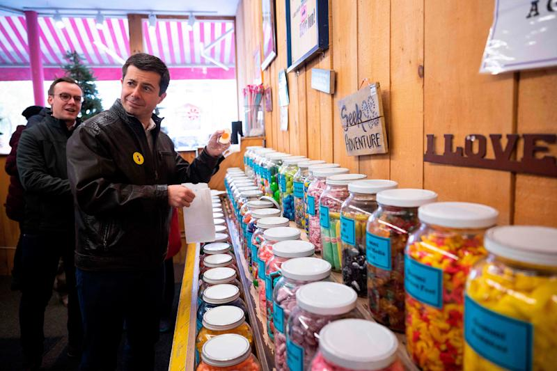 Democratic presidential hopeful Mayor Pete Buttigieg holds up a candy egg as he visits Chutters candy shop in Littleton, NH, on November 10, 2019.